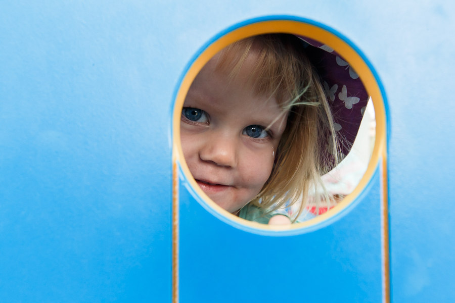 Close up of child peeping through window of play house